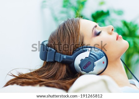 Portrait of resting young woman at home with listening music. Closed eyes. - stock photo