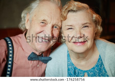 Portrait of retired couple in smart clothes looking at camera - stock photo