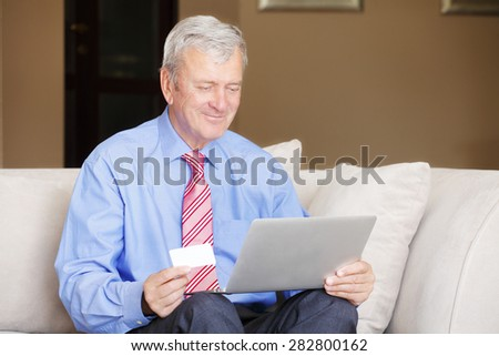 Portrait of retired senior man sitting at sofa while holding credit card in his hands and shopping online with laptop.  - stock photo