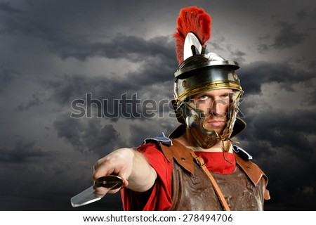 Portrait of Roman soldier brandishing sword over dark clouds - stock photo