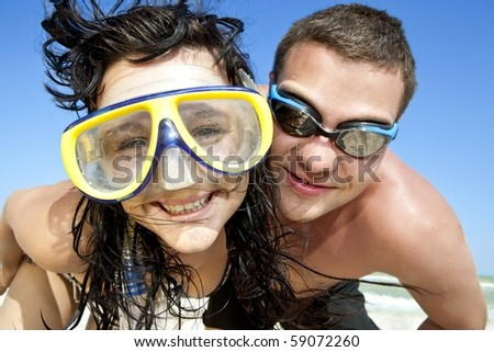 portrait of romantic couple in swimming masks enjoying on the beach - stock photo