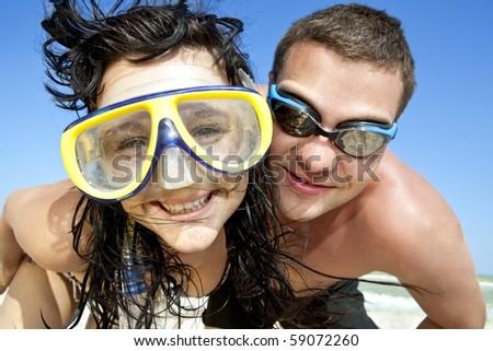 portrait of romantic couple in swimming masks enjoying on the beach - stock photo