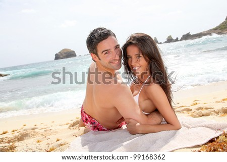 Portrait of romantic couple laying on the beach - stock photo