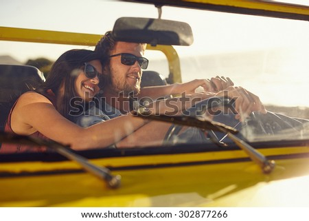 Portrait of romantic young couple going on a long drive in open car on a summer day. Handsome young man with his beautiful girlfriend on a road trip. - stock photo