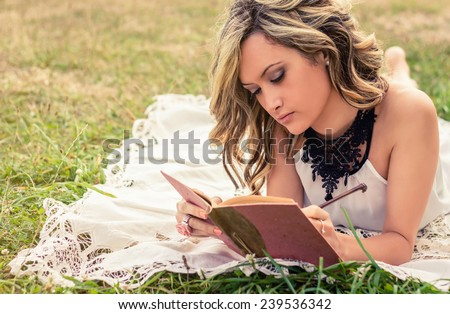 Portrait of romantic young woman writing in a diary lying down over the grass. Relax outdoor time concept. - stock photo