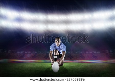 Portrait of rugby player kneeling and holding ball against rugby stadium - stock photo