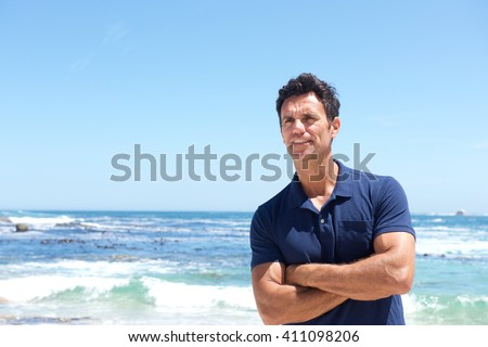 Portrait of rugged middle aged man standing at the beach - stock photo