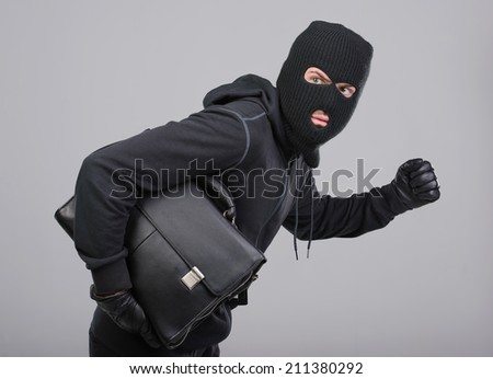 Portrait of running male burglar with a handbag. Isolated on gray background