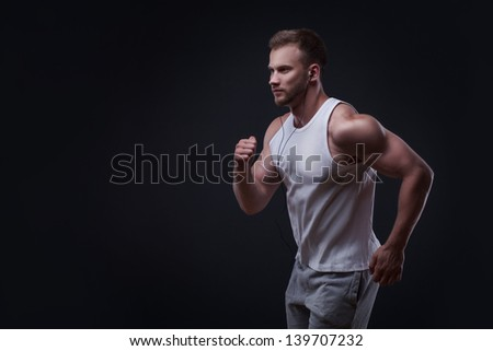 Portrait of running man isolated on black background - stock photo