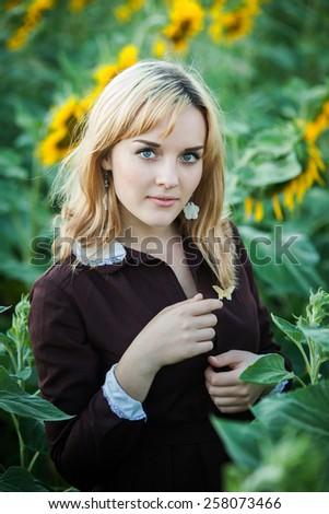 Portrait of russian schoolgirl in the sunflower field - stock photo