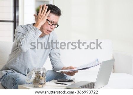 Portrait of 50s mature Asian man having a hard time paying bills. Saving, retirement, retirees financial planning concept. Family living lifestyle at home. - stock photo