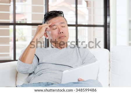 Portrait of 50s mature Asian man headache, pressing on head with tired expression after long period using tablet computer, sitting on sofa at home.