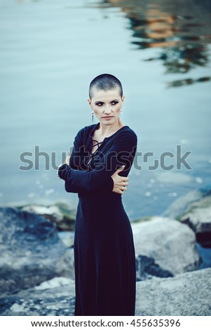 Portrait of sad beautiful Caucasian white young bald girl woman with shaved hair head standing by water lake looking away, mystic dark mood, toned with Instagram filters in blue green color - stock photo