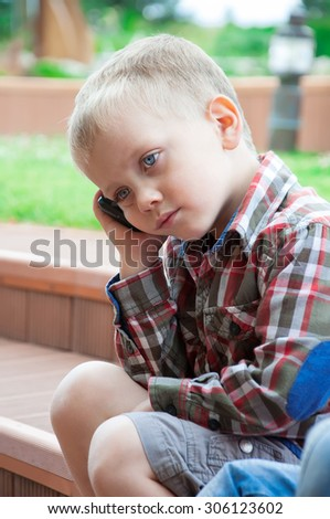 Portrait of sad blond little boy sitting in park and speaking by phone. Sunny and summer  day. Close up. Outdoor shot - stock photo