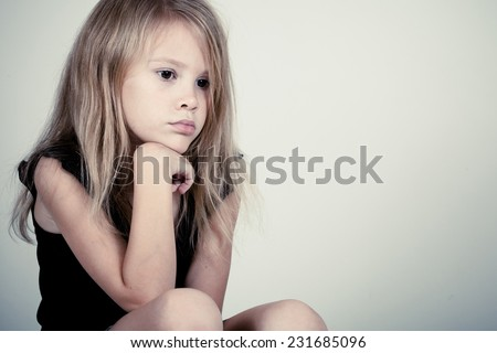 Portrait of sad blond little girl sitting near wall - stock photo