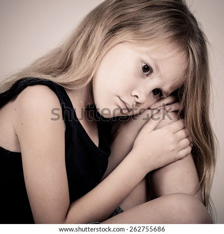 Portrait of sad blond little girl sitting near wall on outdoors at the day time - stock photo