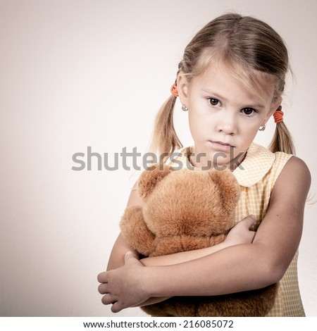 Portrait of sad blond little girl with a toy standing near wall  - stock photo