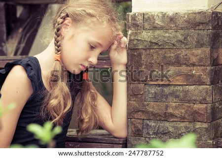Portrait of sad blond teen girl sitting on the stairs at the day time - stock photo