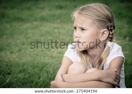 Portrait of sad blonde little girl sitting on the grass at the day time - stock photo
