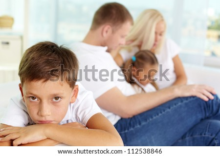 Portrait of sad boy on background of his parents and sister - stock photo
