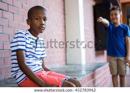 Portrait of sad boy with classmate laughing on him in background at school corridor - stock photo