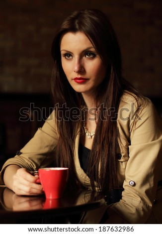 Portrait of sad brunette drinking a cup of coffee - stock photo