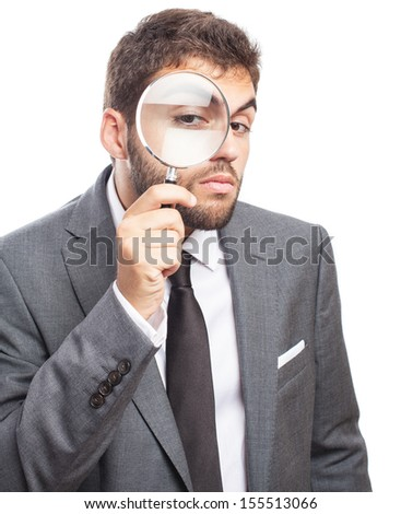 portrait of sad business man looking through a magnifying glass on white