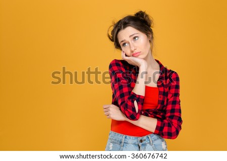 Portrait of sad depressed beautiful young woman in plaid shirt over yellow background - stock photo