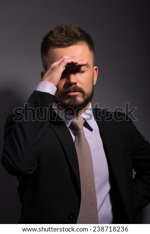 Portrait of sad disappointed  handsome stylish man in elegant black suit and beige tie  touching his forehead closing eyes  waist up - stock photo