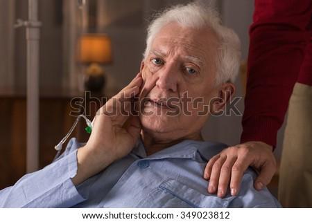 Portrait of sad elderly man suffering from dementia - stock photo