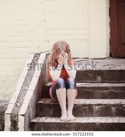 Portrait of sad girl sitting near wall - stock photo