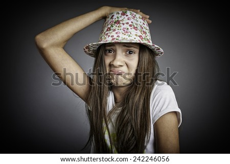 Portrait of sad girl with hand on her colored hat. - stock photo