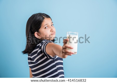 portrait of sad indian girl with a glass of milk, asian girl drinking milk in a glass with sad expressions, portrait of small girl holding a glass of milk over blue background - stock photo