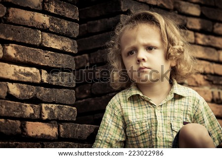 Portrait of sad little boy sitting near the wall at the day time - stock photo
