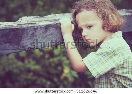 Portrait of sad  little boy standing on the bridge at the day time - stock photo