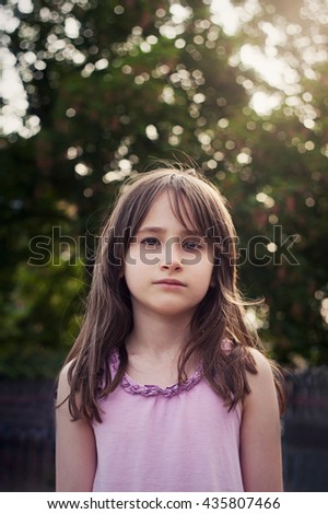Portrait of sad little girl in the summer on a green background with wonderful bokeh - stock photo