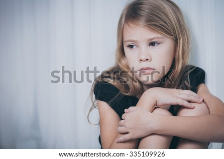 Portrait of sad little girl sitting near the window at home at the day time - stock photo