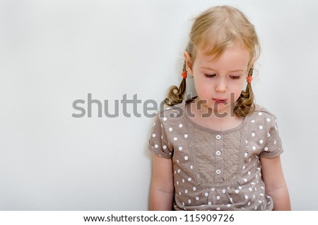 Portrait of sad little girl standing against the wall. Space for text - stock photo