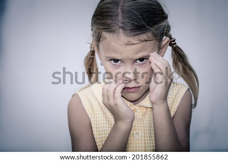 Portrait of sad little girl standing near a wall in the day time - stock photo