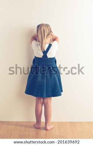 portrait of sad little girl standing near wall. studio shot - stock photo