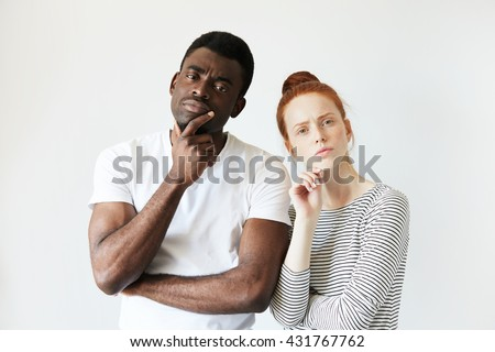 Portrait of sad mixed-race couple. Beautiful Caucasian woman with red hair and handsome African man, looking at the camera with unhappy offended expression, not speaking to each other. Body language - stock photo