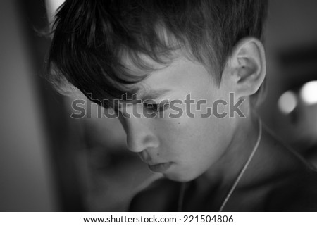Portrait of sad, pensive, serious boy, black and white photo