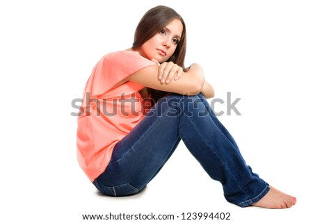 portrait of sad pretty girl sitting on the floor isolated over white background - stock photo