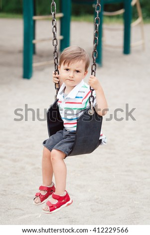 Portrait of sad upset worried little small boy toddler in tshirt and jeans shorts on swing on backyard playground outside on summer day, childhood lifestyle concept - stock photo