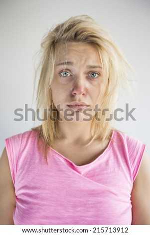 Portrait of sad woman suffering from cold against gray background - stock photo