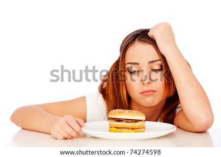 portrait of sad woman with burger over white background - stock photo