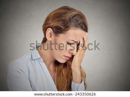 portrait of sad young woman isolated on grey wall background