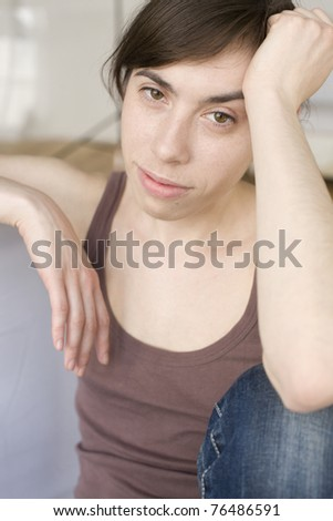 portrait of sad young woman sitting at home - stock photo