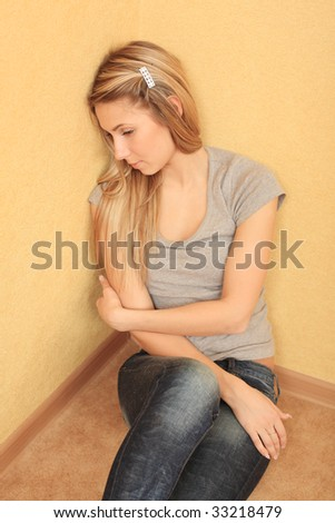 Portrait of sad young woman sitting on a floor at home.
