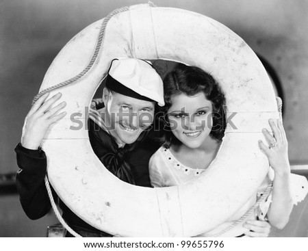 Portrait of sailor and sweetheart with life preserver - stock photo